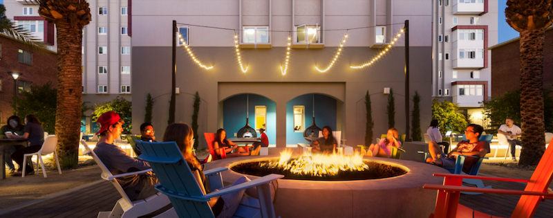 Students sit around a fire at a campus student center