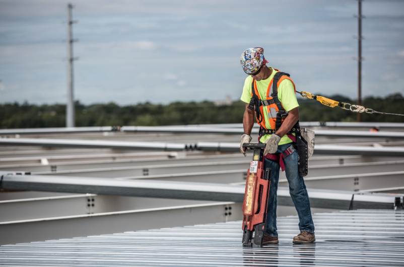 A Barton Malow construction worker installs a metal roof deck.