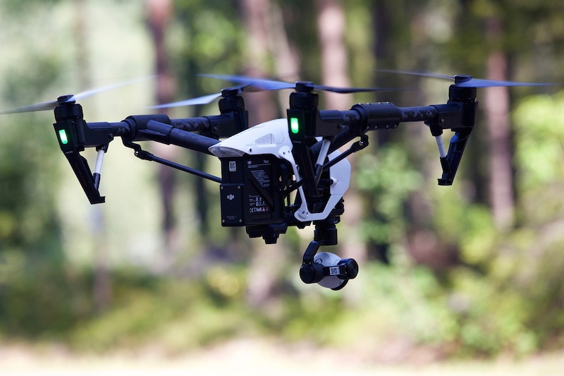 A drone flying in a wooded area