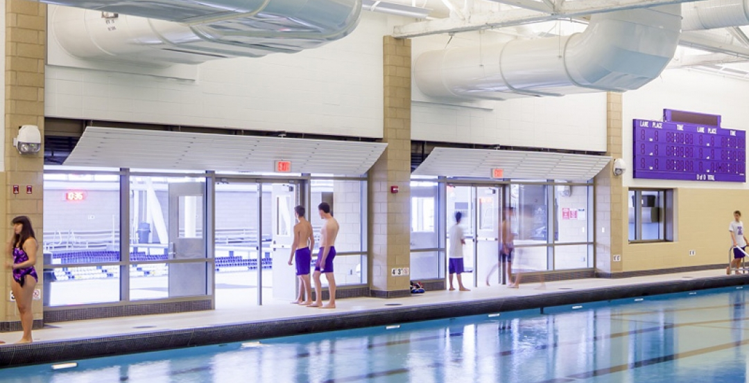Fire-rated glass separation helps merge new and old pools into a single connected aquatics center