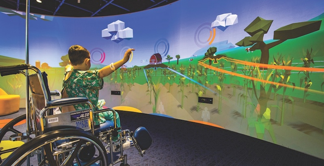 A child uses the Nick's Theater in the Gerdin Family lobby at the Stead Family Children's Hospital
