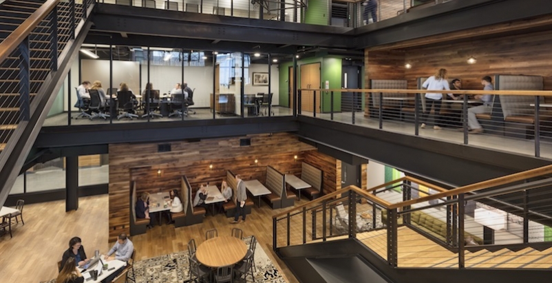A glass-walled conference room overlooks the atrium.