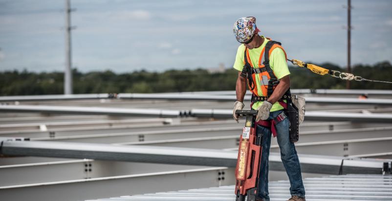 A Barton Malow construction worker installs a metal roof deck.