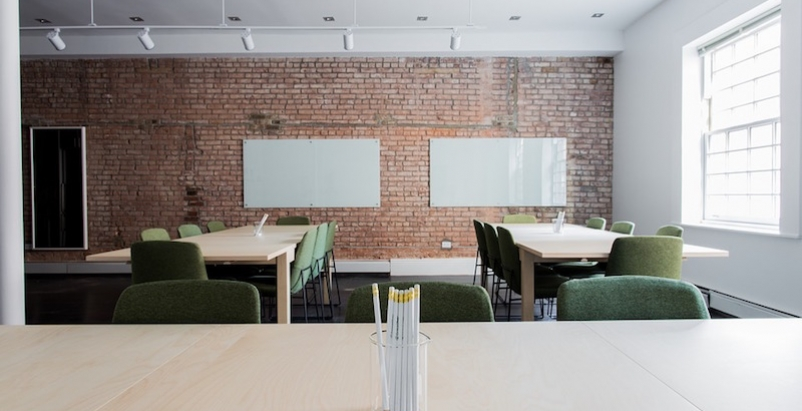 A classroom with large tables and a brick wall