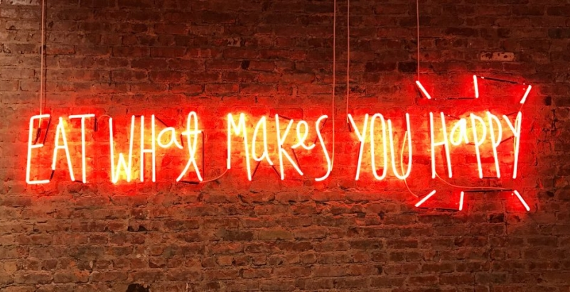 Neon sign with 'Eat what makes you happy' written