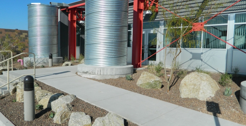 A single-slope metal roof supports an efficient rainwater harvesting system. Twe
