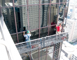 Workers repair a failed glass curtain wall. As glazed curtain walls age, many o
