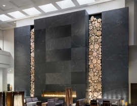 A ceiling-high stone fireplace framed by rustic wooden logs was created by artis