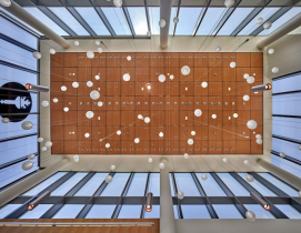 Lighting hanging from a double-height lobby space in the Rohrer College of Business facility