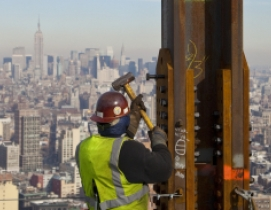 Construction crews set in place a steel horizontal beam at a height (C) CBS News